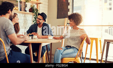 Portrait of a young group of friends meeting in a cafe. Young men and women sitting at cafe table and talking. - Stock Photo