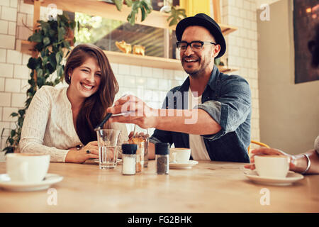 Portrait of happy young man showing his mobile phone to friends while sitting in a cafe. - Stock Photo