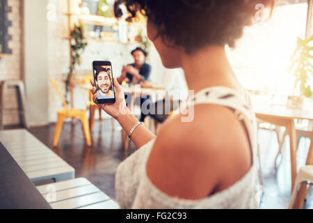 Man and woman talking to each other through a video call on a smartphone. Young woman having a videochat with man - Stock Photo