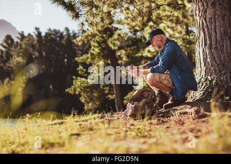 Portrait of senior hiker checking his compass. Mature man sitting by a tree searching for direction. - Stock Photo