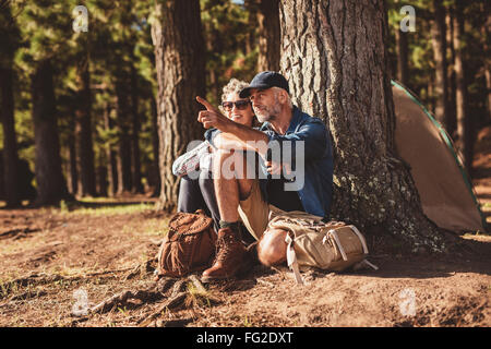Portrait of mature couple relaxing at their campsite with man showing something to woman. Senior couple hiking and - Stock Photo