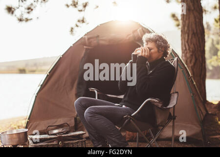 Portrait of mature woman sitting in chair at campsite drinking coffee. Caucasian woman camping in nature on summer - Stock Photo