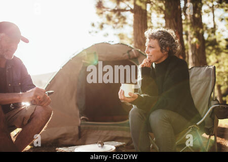 Portrait of relaxed mid adult couple sitting outside tent while camping nearby lakeside on a sunny day. Woman holding - Stock Photo