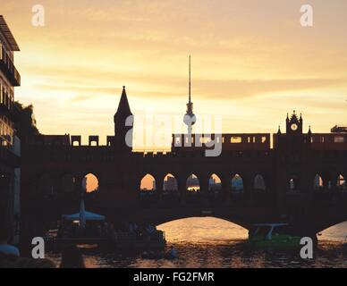 Oberbaum Bridge Over Spree River Against Fernsehturm During Sunset - Stock Photo