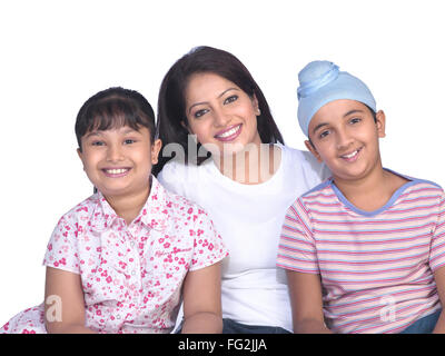 Sikh lady with children sitting close to each other MR#702Z;702Y;702X - Stock Photo