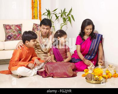 Mother arranging diyas with family looking at her sitting in house MR#702R,MR#702S,MR#702T,MR#702U - Stock Photo