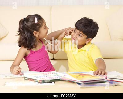 Brother and sister doing naughty expression sitting in house MR#702T, MR#702U - Stock Photo