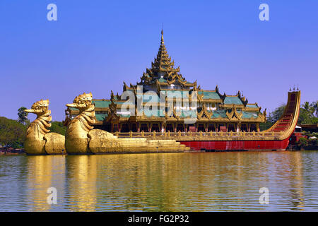 Karaweik Palace floating restaurant, Kandawgyi Lake, built in the shape of a Royal Barge, Yangon, Myanmar - Stock Photo