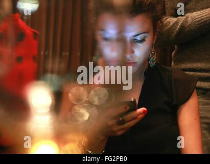 Young Woman Using Mobile Phone At Restaurant - Stock Photo