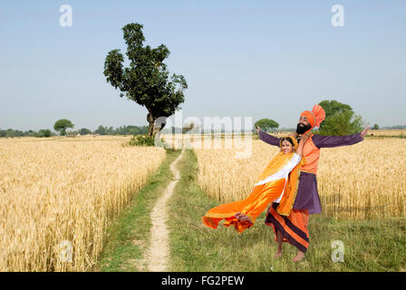 Dancers performing folk dance bhangra in wheat field MR#779E;779C - Stock Photo