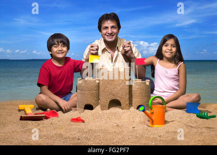 Father holding hand of children at sandcastle on seashore MR#779H;779G;477 - Stock Photo