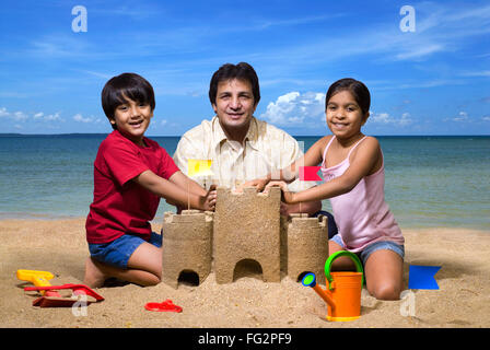 Father with children at sandcastle on seashore MR#779H;779G;477 - Stock Photo