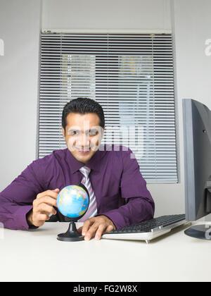 Executive showing globe on desk MR#779K - Stock Photo