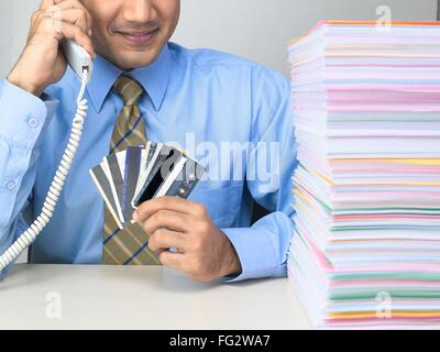 Multitasking executive talking on telephone with showing credit cards MR#779K - Stock Photo