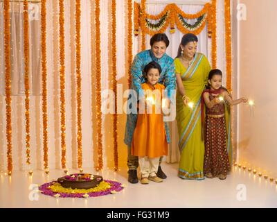 Indian family celebrating Diwali festival of lights India - model released MR#779P, MR#779Q, MR#779R, MR#779S - Stock Photo