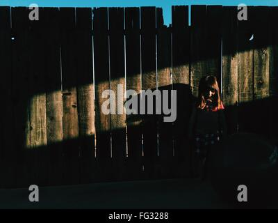 Girl Standing Against Fence - Stock Photo