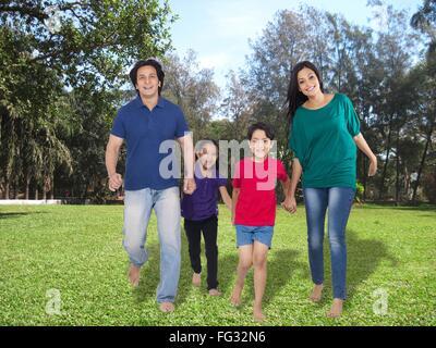 Parent with children on grass lawn ; Mumbai; India; Asia MR#779P ; MR#779Q ; MR#779R ; MR#779S - Stock Photo