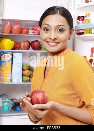 Young lady kept red apple in hand palm standing at open refrigerator MR#702U - Stock Photo