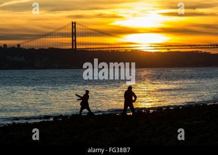 Silhouette People Standing By Sea With Ponte 25 De Abril Bridge Against Sunset Sky - Stock Photo