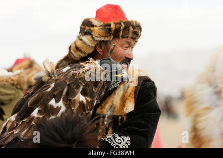 Golden eagle and its handler at the Golden Eagle Festival near Ulgii in far western Mongolia. - Stock Photo
