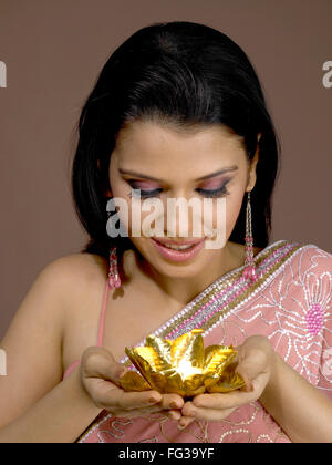 South Asian Indian woman smiling and golden colour diya on hand palms MR # 702 - Stock Photo