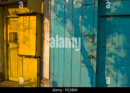 Old wooden yellow and blue locked doors ; Bhowanipur ; Calcutta ; West Bengal ; India - Stock Photo