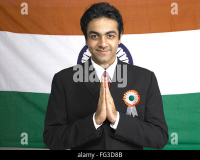 Executive in welcome pose standing in front of national flag of India MR#702A - Stock Photo
