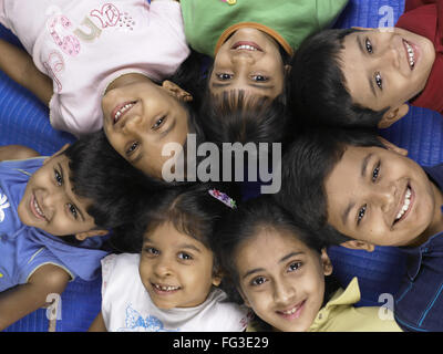 South Asian Indian boys and girls lay down on floor in nursery school MR - Stock Photo