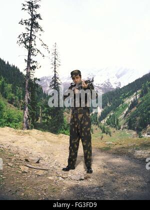 Indian army soldier Ak 47 machine gun in hand mountain in background MR - Stock Photo