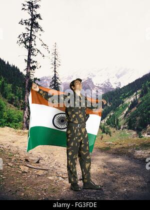Indian army soldier holding national flag on his backside mountain in background MR - Stock Photo