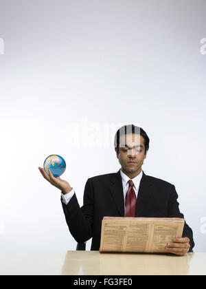 Businessman holding globe in hand and reading newspaper MR - Stock Photo