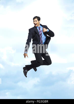 Executive jumping with joy in blue sky MR - Stock Photo
