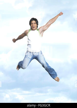 Man jumping with joy in blue sky MR - Stock Photo