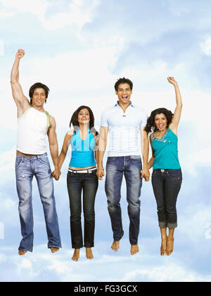 Couples jumping with joy in blue sky MR - Stock Photo