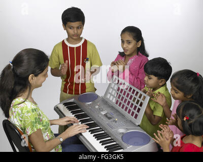 South Asian Indian teacher playing keyboard and children singing in nursery school MR - Stock Photo