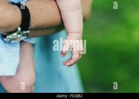 Midsection Of Father Holding Baby - Stock Photo
