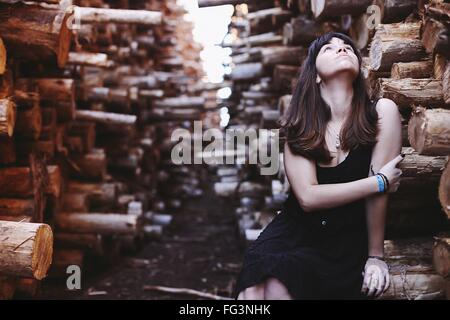 Woman Sitting On Woods Looking Up Holding Arms Outdoors