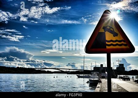 Road Sign By River Against Sky - Stock Photo