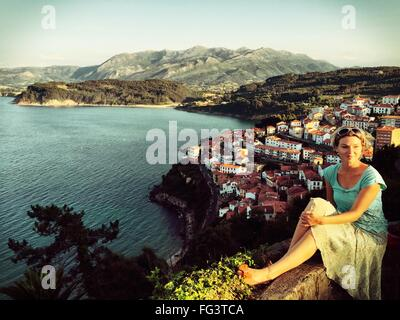 Smiling Young Woman Sitting On Retaining Wall At Hill By Sea - Stock Photo