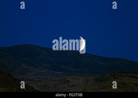 Lunar eclipse rising in the night sky above Boise, Idaho, USA. - Stock Photo