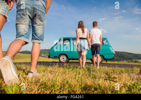 Couples in love, nature, blue sky, campervan, back view - Stock Photo