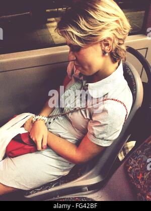 High Angle View Of Woman Relaxing On Seat While Travelling In Bus - Stock Photo