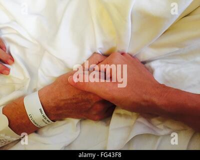 Cropped Image Of Man Holding Woman Hand On Bed At Home - Stock Photo