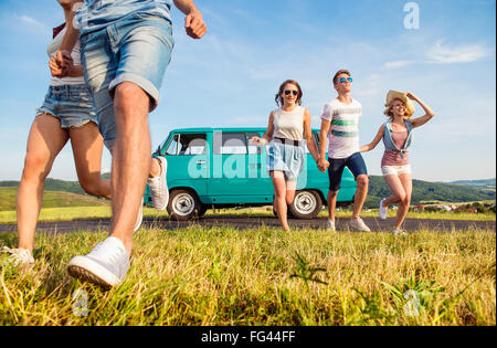 Running teenage couples in love outside against blue sky - Stock Photo