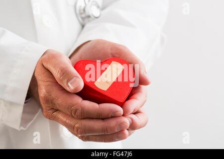 Doctor holding plastic heart with adhesive bandage - Stock Photo