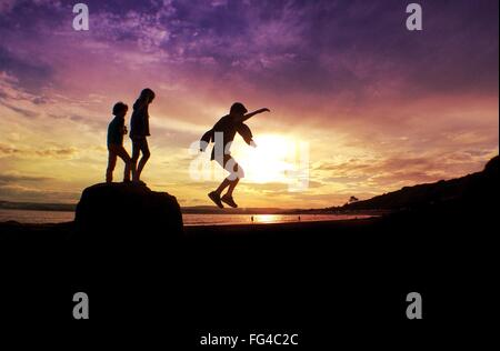 Silhouette Friends Enjoying On Beach Against Orange Sky - Stock Photo