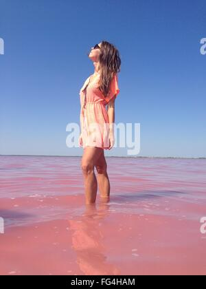 Low Angle View Of Young Woman Wearing Orange Dress Standing In Sea Against Clear Blue Sky - Stock Photo