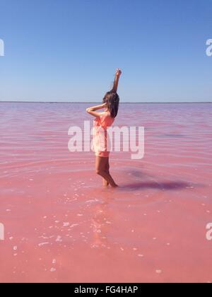 Young Woman Wearing Orange Dress Standing In Sea Against Clear Blue Sky - Stock Photo