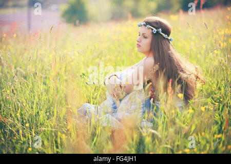 Young woman enjoying spring weather in flower field . Hippie and gypsy dress - Stock Photo