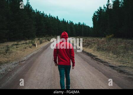 Rear View Of Man Walking On Country Road - Stock Photo